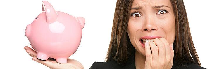 Nervous business owner holding piggy bank