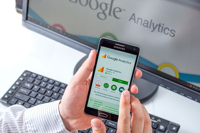 Desktop and phone with screens showing Google Analytics.