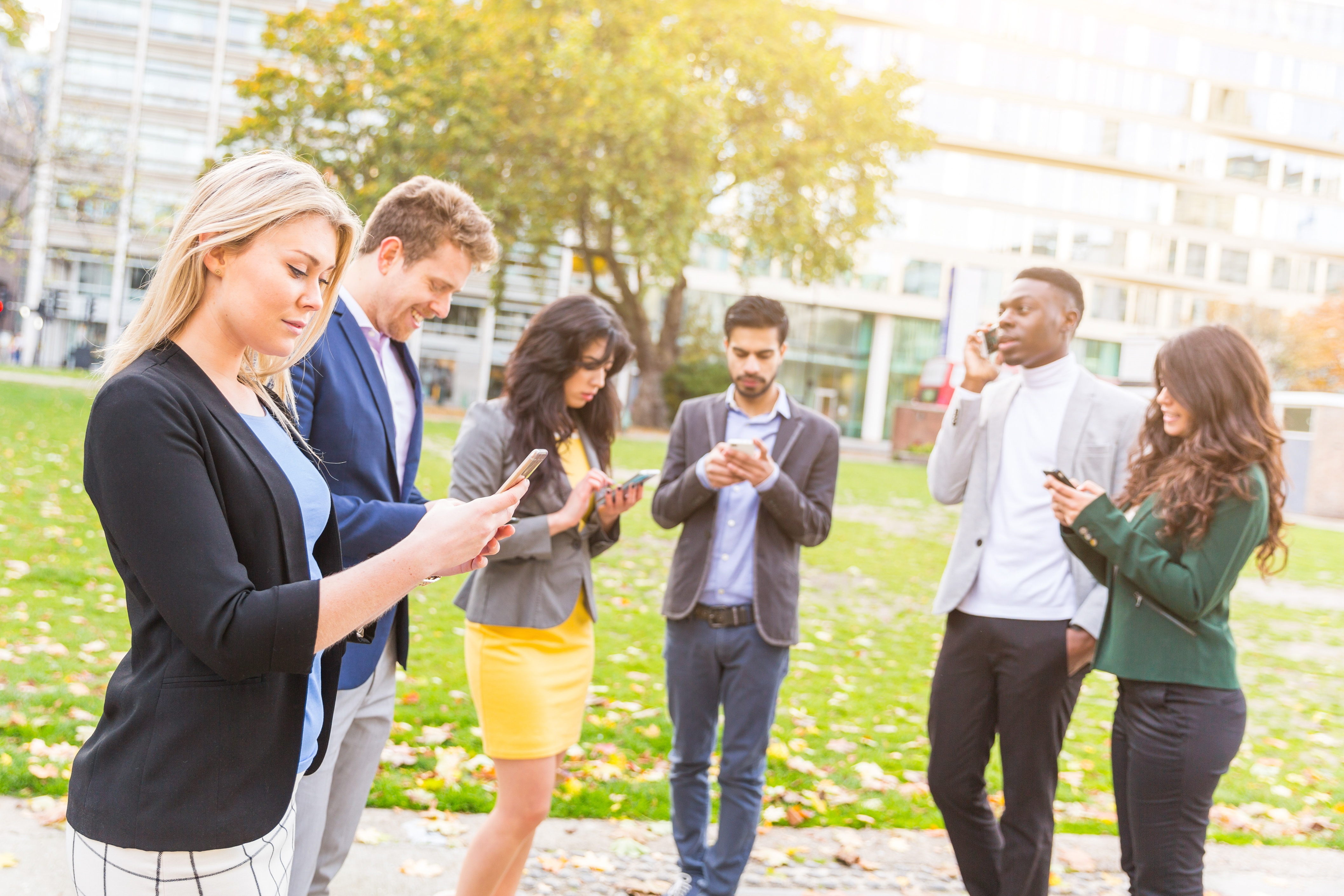 Group of people outdoors on cell phones.