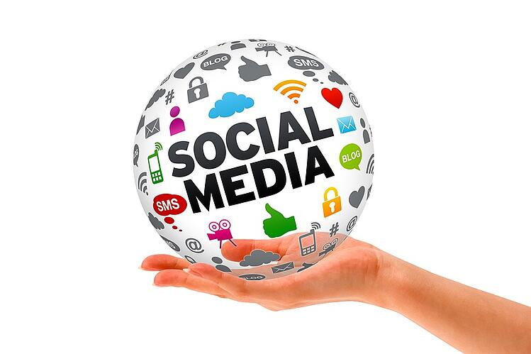 Hand holding a ball with social media icons.