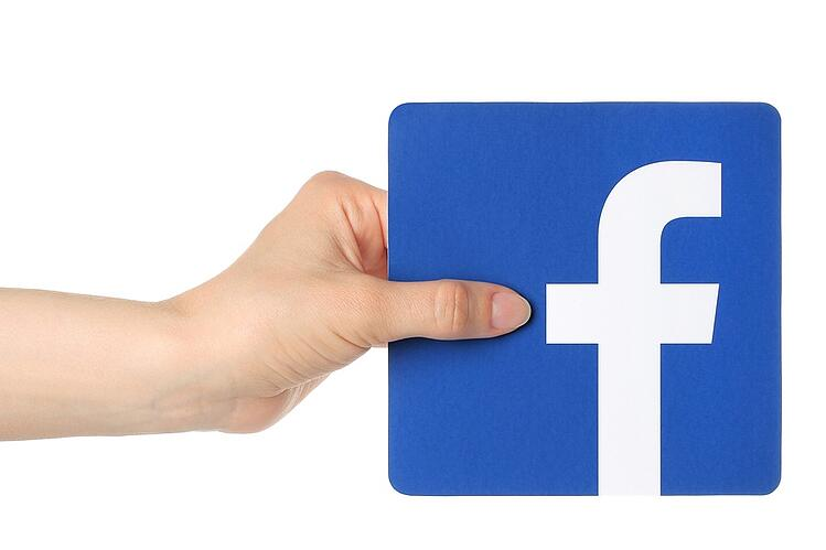 Hand holding facebook icon