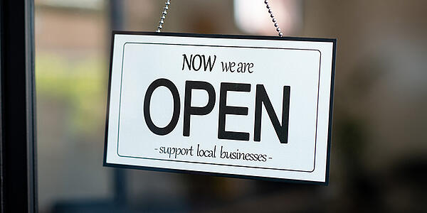 Image of a Now We Are Open sign hanging in the window of a storefront.